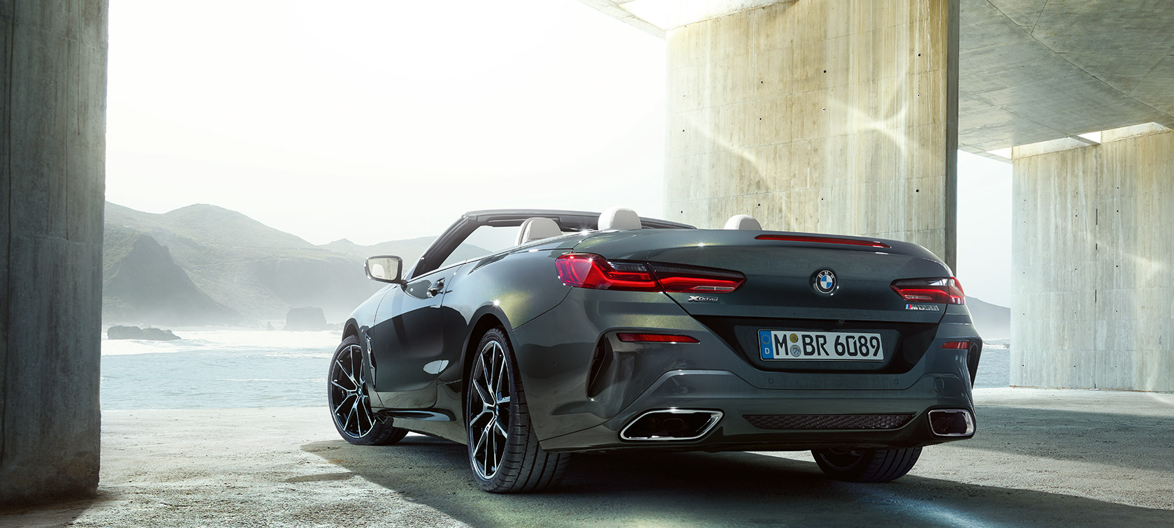 BMW M850i xDrive Dravit Grey metallic, three-quarter view from rear left.