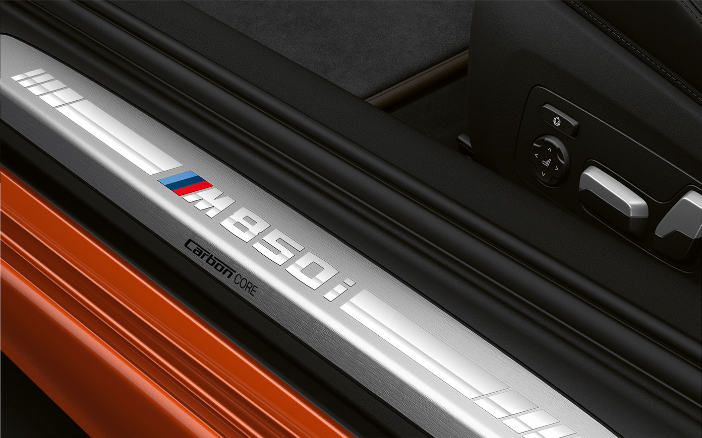 Close-up of the door sill of the BMW 8 Series Coupé with M850i logo.