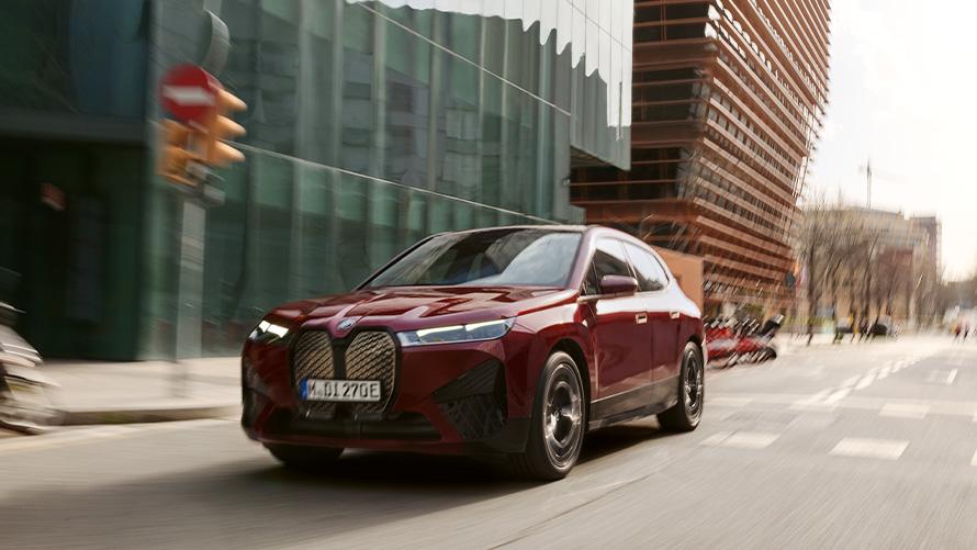 BMW iX i20 2021 electric SUV BMW iX xDrive50 Aventurin Red driving in urban sorroundings