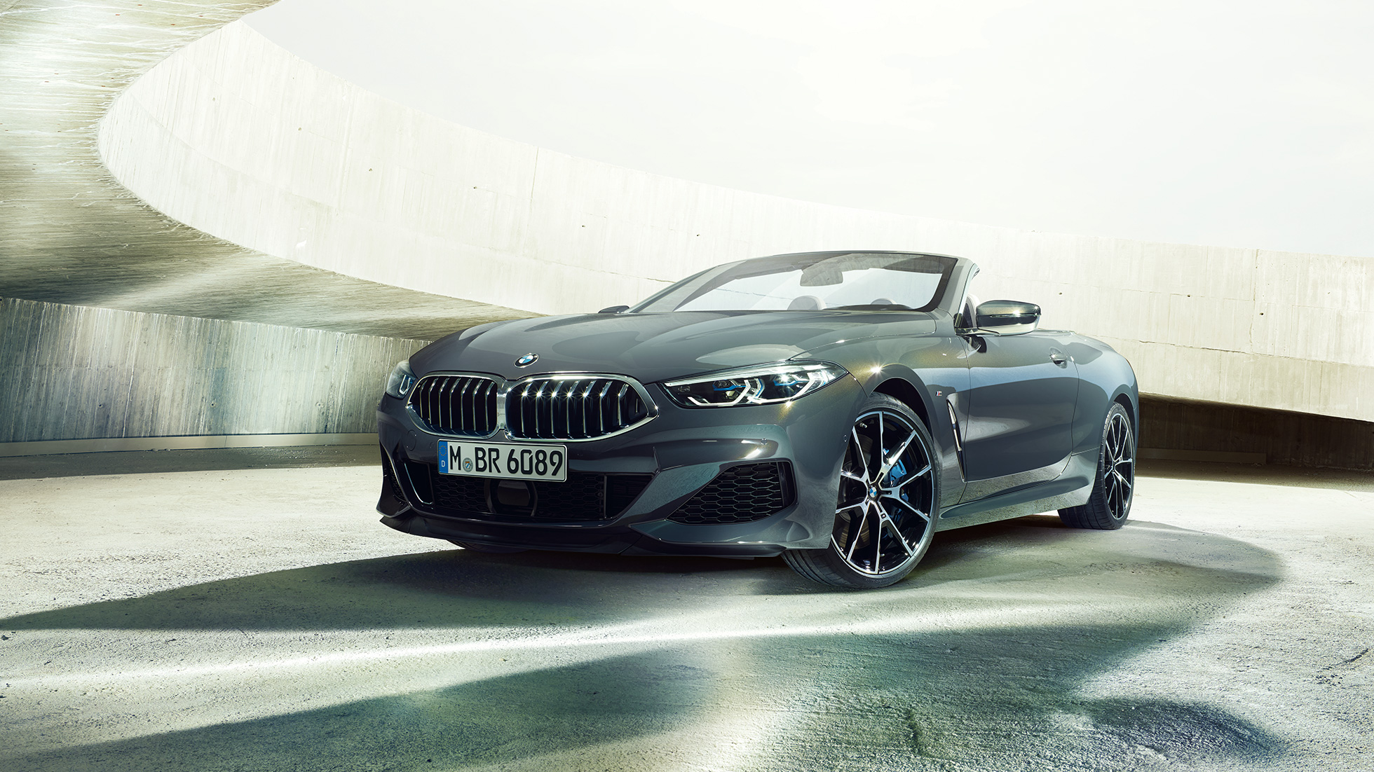 BMW M850i xDrive Convertible in Dravit Grey metallic with open softtop, three-quarter front view, standing in concrete building.