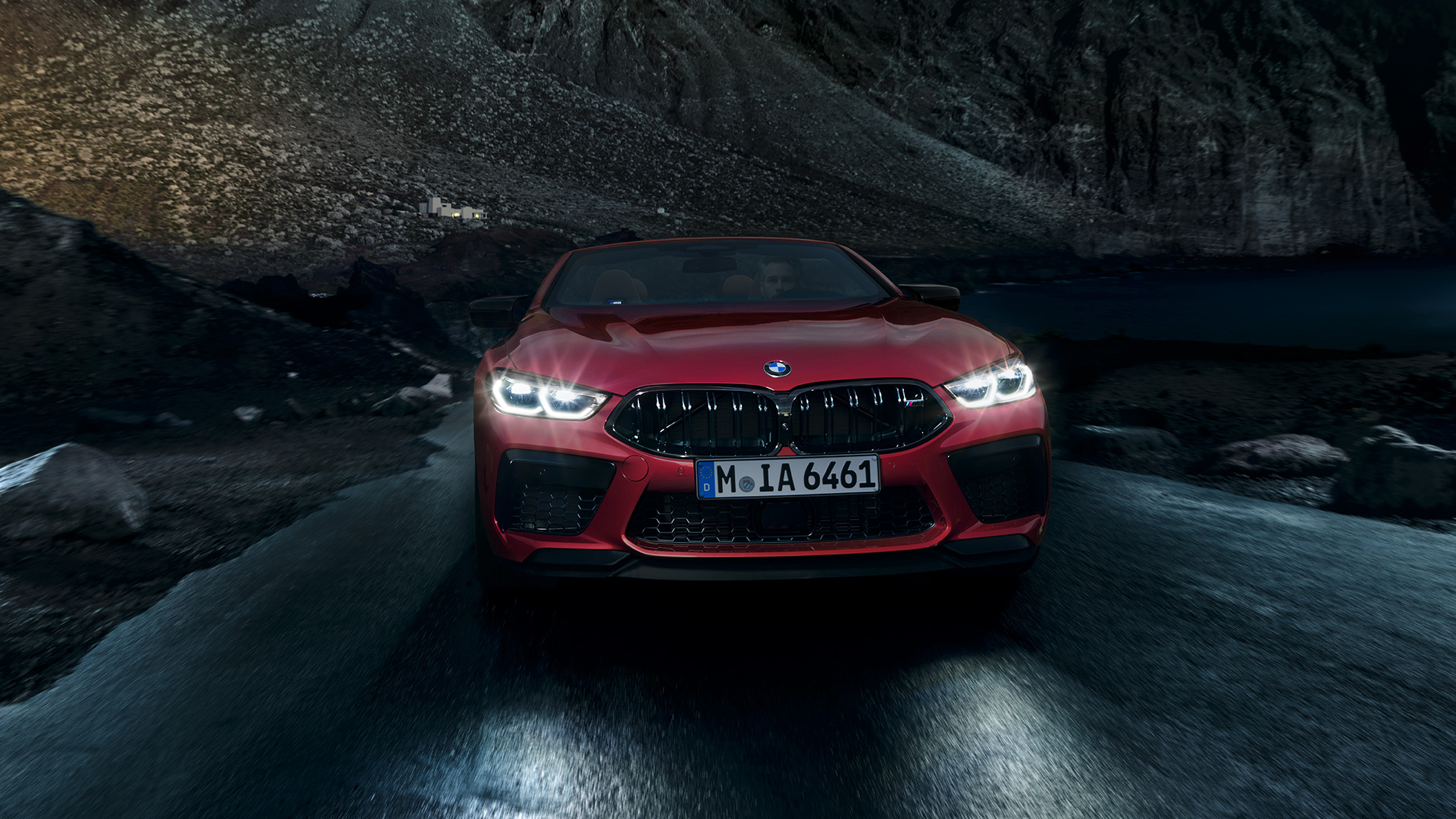 BMW M8 Competition Convertible in Motegi Red metallic with shining headlights, front view, driving at night.