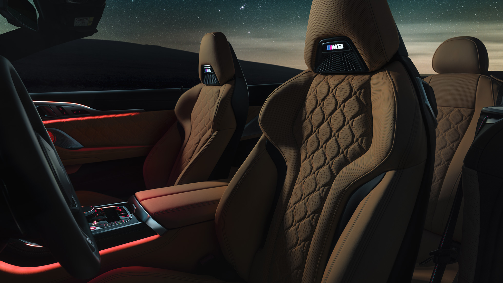 BMW M8 Competition Convertible with open softtop under starry sky, interior with M Sport seats in leather 'Merino' and red ambient light.