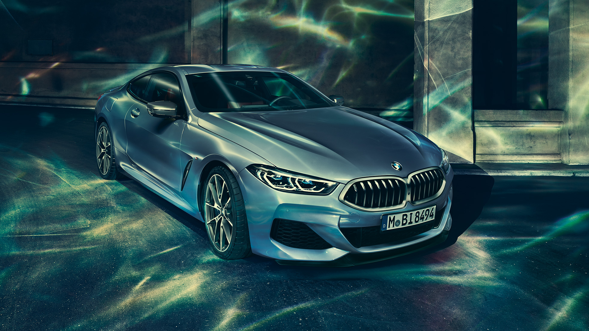 BMW M850i xDrive Coupé in Barcelona Blue metallic, three-quarter front view left, standing in front of building.