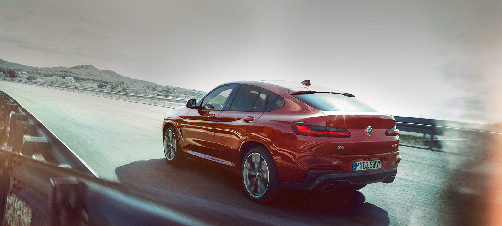 BMW X4 M40i G02 2018 Flamenco Red brilliant effect three-quarter rear view driving on the road